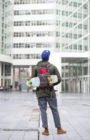 Skateboarder  looking at building