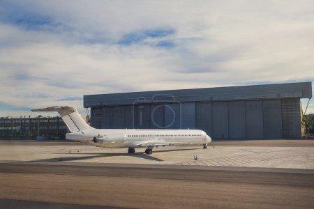 Photo pour Un biréacteur bimoteur blanc uni sur le tarmac devant un grand hangar - image libre de droit