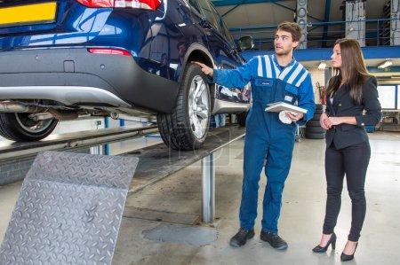 Photo pour Mécanicien de service dédié et professionnel montrant une cliente autour de sa voiture, qui vient d'être entretenue et équipée de pneus d'hiver . - image libre de droit