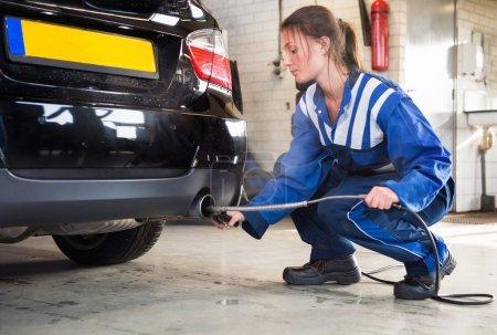 Female mechanic probing a sensor