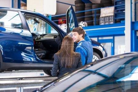 Photo pour Un mécanicien de vente montrant le véhicule sur lequel il a travaillé à une femme d'affaires, qui est intéressé à l'acheter dans un garage de concessionnaire de voitures d'occasion - image libre de droit