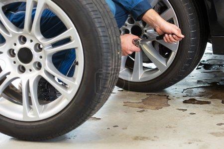 mechanic tightening the wheel nuts