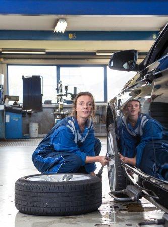 Female mechanic, loosening bolts