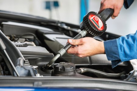 sedan gets an oil change by a mechanic