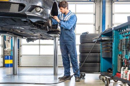 Photo pour Mécanicien masculin réparation de voiture sur ascenseur hydraulique dans le garage - image libre de droit