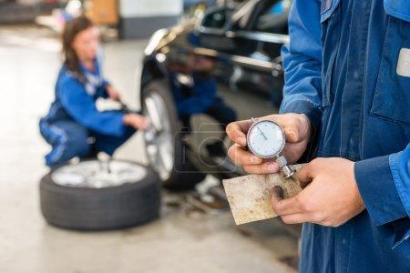 Mechanic holding gauge In Garage