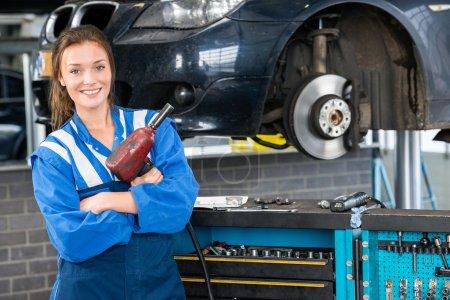 Photo pour Heureux mécanicien femelle avec commandes pneumatiques clé en voiture dans le garage - image libre de droit