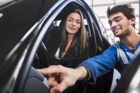 Photo pour Mécanicien et le client dans le garage à la recherche de voiture - image libre de droit
