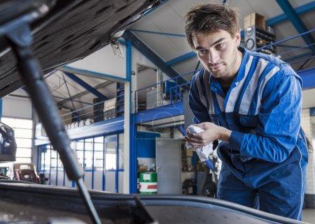 Photo pour Mécanicien regarde sous le capot d'une voiture - image libre de droit