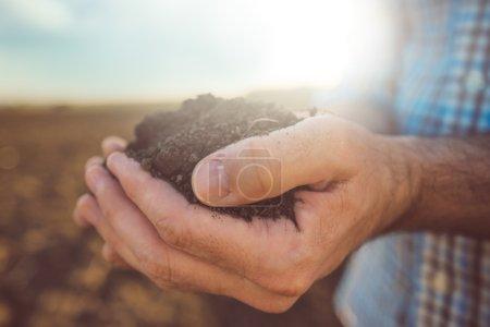 Landwirt hält Haufen von Ackerboden, aus nächster Nähe