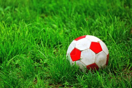 Old soccer ball in grass