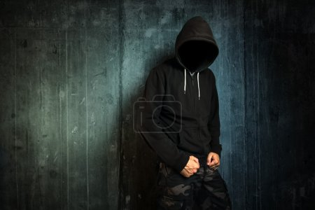 Photo for Dangerous unrecognizable faceless criminal standing in front of concrete wall, crime rate and gangster lifestyle concept. - Royalty Free Image
