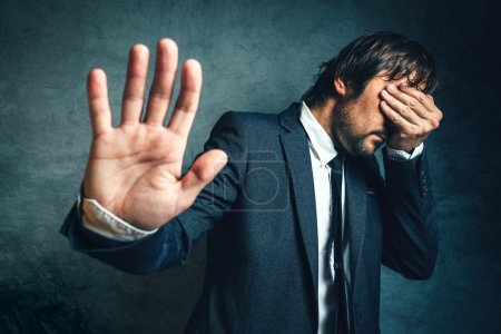 Photo for Stressed businessman after business project failure, covering eyes in despair and hand gesturing stop to camera. - Royalty Free Image