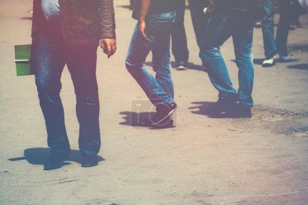 Retro toned image of pedestrians walking the street