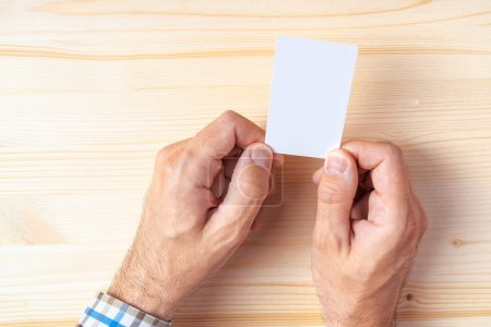 Top view of businessman holding blank business card