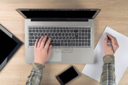 Photo for Female programmer writing notes on piece of paper while typing laptop keyboard, top view. - Royalty Free Image
