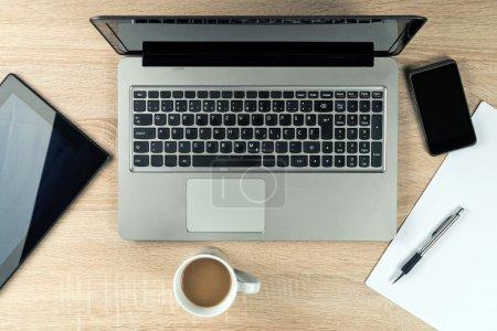 Foto de Mesa de oficina con ordenador portátil, tablet digital, móvil smartphone y taza de café. - Imagen libre de derechos
