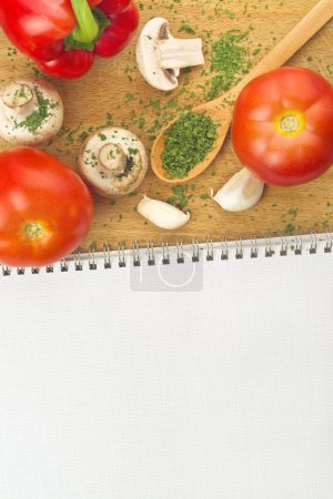 Photo for Garlic, Parsley, Mushroom, Tomato And Paprika with Recipe Book on wooden board in the kitchen. Food preparation background. - Royalty Free Image