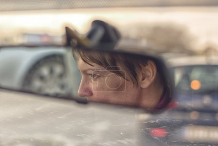 Photo for Female Face in Car's Rear View Mirror while driving through the city traffic rush hour - Royalty Free Image