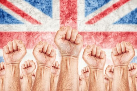 Photo pour Great Britain Labour movement, workers union strike concept with male fists raised in the air fighting for their rights, British national flag in out of focus background. - image libre de droit