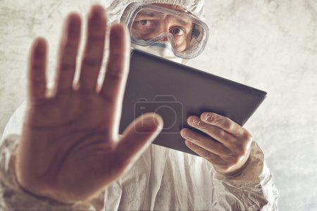 Photo for Chemical Scientist Holding Digital Tablet Computer and Gesturing Stop Sign. Chemical disaster, pollution or virus threat conceptual image with selective focus and shallow DOF. - Royalty Free Image