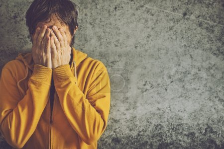 Photo for Upset Depressive Adult Man Wearing Yellow Jacket is Crying with his Face Covered. - Royalty Free Image