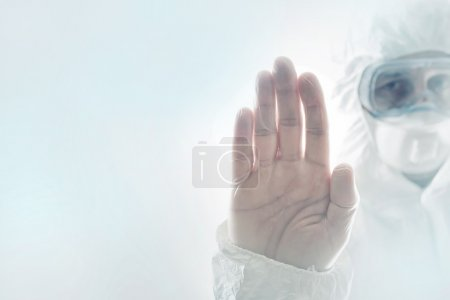 Photo for Chemical Scientist Gesturing Stop Sign with his Hand Raised in the Air, while wearing a protective clothing. Chemical disaster, pollution or virus threat conceptual image with selective focus and shallow DOF. - Royalty Free Image