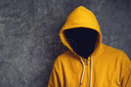 Photo for Faceless unknown and unrecognizable person without identity wearing yellow hooded jacket. - Royalty Free Image