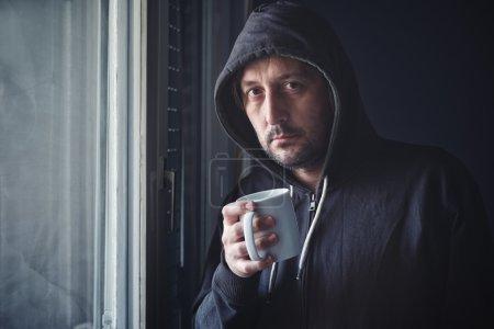 Photo pour Homme adulte avec veste à capuchon tenant tasse de café chaud par la fenêtre, boisson et faire des plans pour la journée à venir. Focus sélectif avec faible profondeur de champ . - image libre de droit