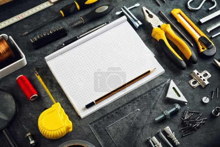 Photo for Assorted Do It Yourself DIY Tools and Blank Page Notebook as Copy Space for Home Improvement Project Planning or any Other Workshop Message. - Royalty Free Image