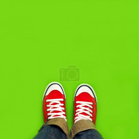 Photo for Springtime Youth Lifestyle Concept for New Beginnings, Woman with Red Sneakers Standing on Green Spring Background as Blank Copy Space. - Royalty Free Image