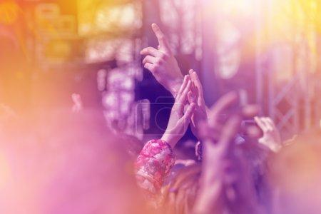 Photo pour Les fans applaudissent au groupe de musique pour avoir donné un concert sur scène dans l'Open Arena, mise au point sélective image tonique avec Sunflares . - image libre de droit