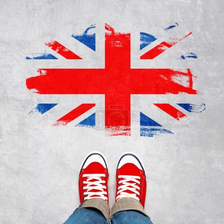 Photo pour British Urban Youth Concept, Feet in Red Sneakers from Above Standing in front of Grunge Great Britain Flag British Concept, Feet in Red Sneakers from Above Standing in front of Grunge Great Britain Flag British. - image libre de droit