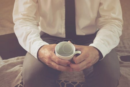 Lonely Businessman in hotel room with empty Coffee Cup