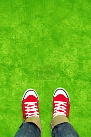 Feet From Above, Teenager in Sneakers Standing on Green Backgrou