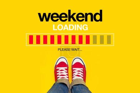 Foto de Fin de semana cargando contenido con una persona joven que lleva zapatillas rojas desde arriba de pie frente a la barra de progreso de carga, esperando el final de la semana, Top View - Imagen libre de derechos
