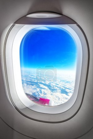 Airplane Porthole Window and Summer Clouds