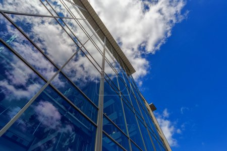 Modern Office Building with Clouds Reflecting on Glass Facade