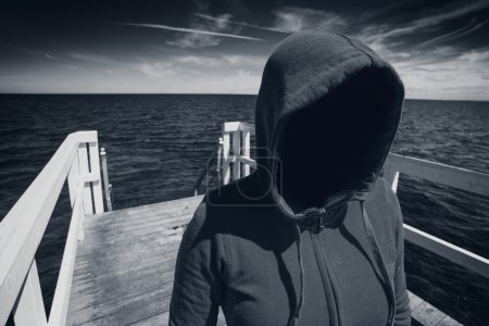 Photo for Abduction Concept, Faceless Hooded Unrecognizable Woman at Ocean Pier, Unknown Spooky Female, Black and White Image - Royalty Free Image