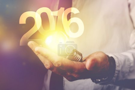 Photo for Happy new 2016 business year, businessman with light bulb and number 2016, retro toned image, selective focus. - Royalty Free Image