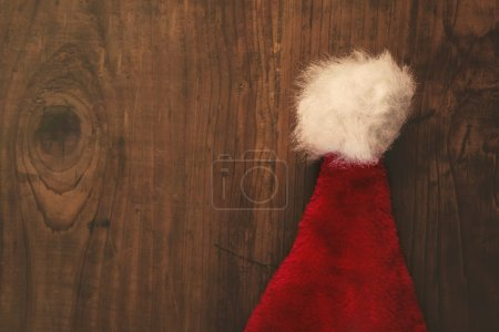 Photo for Retro toned Santa Claus hat on wooden desk with blank copy space, top view - Royalty Free Image