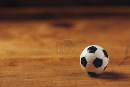 Miniature plastic soccer ball on wooden table