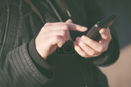 Photo for Woman texting SMS message on mobile phone, female person in winter jacket using telephone outdoors, retro toned image with selective focus on hands - Royalty Free Image