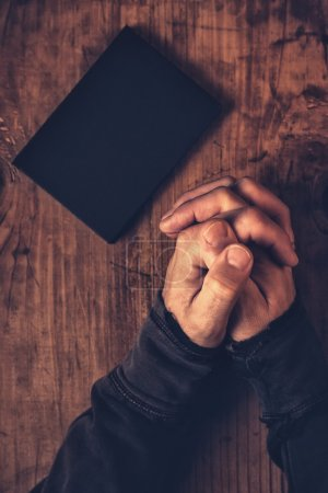Photo for Folded hands of Christian man praying with Holy Bible by his side on wooden desk in church, top view - Royalty Free Image