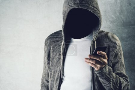 Photo for Faceless hooded person using mobile phone, unrecognizable male with smartphone, identity theft and technology crime concept. - Royalty Free Image
