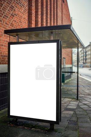 Photo pour Panneau publicitaire d'arrêt d'autobus blanc sur la rue vide comme espace de copie pour l'annonce extérieure d'affiche maquette vers le haut. - image libre de droit