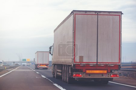 Commercial trailer truck in motion on freeway on cloudy afternoo