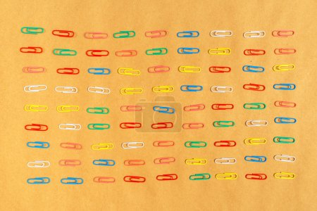 Flat lay colorful paper clips arrangement on kraft paper backgro