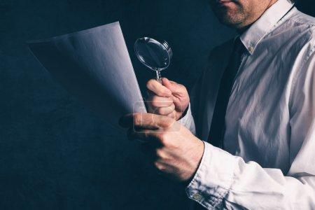 Photo pour Inspecteur de faire un audit financier, homme d'affaires lu affaires rapport ou contrat notes avertissement avec loupe, rétro tonique, mise au point sélective d'impôt - image libre de droit