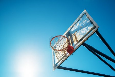 Photo for Plexiglass street basketball board with hoop on outdoor court against blue sunny sky as copy space. - Royalty Free Image